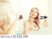 Купить «woman with styling iron doing her hair at bathroom», фото № 26520340, снято 13 февраля 2016 г. (c) Syda Productions / Фотобанк Лори