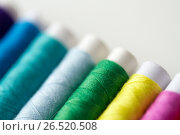 Купить «row of colorful thread spools on table», фото № 26520508, снято 29 сентября 2016 г. (c) Syda Productions / Фотобанк Лори