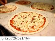 Купить «raw pizza with grated cheese on table at pizzeria», фото № 26521164, снято 17 февраля 2017 г. (c) Syda Productions / Фотобанк Лори