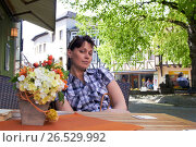 Stylish young female wearing casual shirt sitting in open air at table enjoying aroma of flowers having happy expression with charming eyes. Стоковое фото, фотограф Kirill Medvedev / Фотобанк Лори