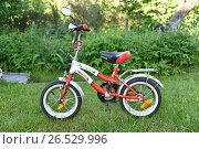 Купить «Детский  велосипед на газоне», эксклюзивное фото № 26529996, снято 11 июня 2017 г. (c) Юрий Морозов / Фотобанк Лори
