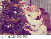 Купить «Family decorating Christmas tree at home», фото № 26530400, снято 17 ноября 2018 г. (c) Яков Филимонов / Фотобанк Лори
