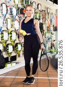 Купить «Female standing in sporting goods store with balls and racket», фото № 26535876, снято 15 мая 2017 г. (c) Яков Филимонов / Фотобанк Лори