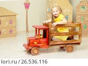 Купить «Little girl is riding a toy wooden car», фото № 26536116, снято 28 апреля 2017 г. (c) Сергей Колесников / Фотобанк Лори