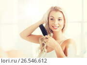 Купить «happy woman brushing hair with comb at bathroom», фото № 26546612, снято 13 февраля 2016 г. (c) Syda Productions / Фотобанк Лори