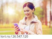 Купить «smiling woman calling on smartphone in park», фото № 26547120, снято 10 мая 2015 г. (c) Syda Productions / Фотобанк Лори