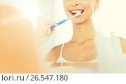 Купить «woman with toothbrush cleaning teeth at bathroom», фото № 26547180, снято 13 февраля 2016 г. (c) Syda Productions / Фотобанк Лори