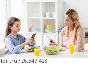 Купить «sad woman looking at her daughter with smartphone», фото № 26547428, снято 26 марта 2017 г. (c) Syda Productions / Фотобанк Лори