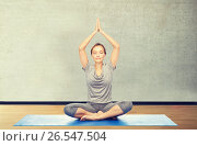 Купить «woman making yoga meditation in lotus pose on mat», фото № 26547504, снято 13 ноября 2015 г. (c) Syda Productions / Фотобанк Лори