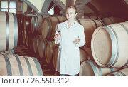 Купить «Female wine house worker checking quality of product», фото № 26550312, снято 21 сентября 2016 г. (c) Яков Филимонов / Фотобанк Лори