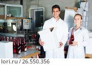 Купить «Two cheerful employees standing in packaging section on wine manufactory», фото № 26550356, снято 21 сентября 2016 г. (c) Яков Филимонов / Фотобанк Лори