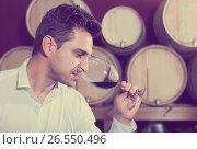 Купить «Customer holding glass of red wine and tasting in winery section», фото № 26550496, снято 20 августа 2018 г. (c) Яков Филимонов / Фотобанк Лори