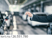 Купить «Giving a key from new car at dealership showroom», фото № 26551780, снято 2 июня 2017 г. (c) Andrejs Pidjass / Фотобанк Лори