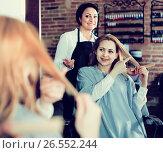 Купить «Woman points to master in hairdress salon right hair length for haircut», фото № 26552244, снято 7 марта 2017 г. (c) Яков Филимонов / Фотобанк Лори
