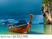 Купить «A Thai boat with a long tail near the shore, a blue rain cloud over the Andaman Sea», фото № 26552900, снято 6 ноября 2016 г. (c) Константин Лабунский / Фотобанк Лори
