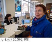 """Пожилая женщина с паспортом у стойки в офисе компании """"Ростелеком"""" (2017 год). Редакционное фото, фотограф Вячеслав Палес / Фотобанк Лори"""