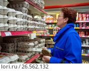 Пожилая женщина стоит у полок с куриными яйцами в продуктовом магазине (2017 год). Редакционное фото, фотограф Вячеслав Палес / Фотобанк Лори