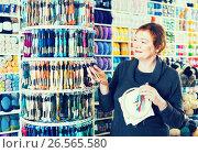Купить «Woman choosing mouline for embroidery in needlework shop», фото № 26565580, снято 10 мая 2017 г. (c) Яков Филимонов / Фотобанк Лори