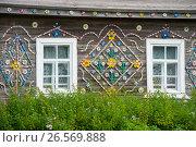 Купить «Старый деревянный дом, украшенный рисунком из старых пластиковых крышек», фото № 26569888, снято 8 августа 2016 г. (c) Pukhov K / Фотобанк Лори
