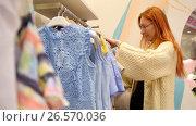 Купить «Red hair woman in a clothing store chose a dress - shopping concept», видеоролик № 26570036, снято 18 января 2020 г. (c) Константин Шишкин / Фотобанк Лори