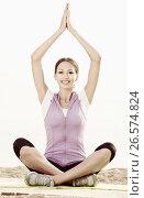 Купить «Young smiling woman practise yoga cross-legged», фото № 26574824, снято 22 октября 2018 г. (c) Яков Филимонов / Фотобанк Лори