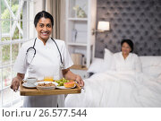 Купить «Nurse holding breakfast tray while patient lying on bed at home», фото № 26577544, снято 15 марта 2017 г. (c) Wavebreak Media / Фотобанк Лори