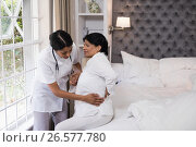 Nurse assisting female patient suffering with back pain on bed. Стоковое фото, агентство Wavebreak Media / Фотобанк Лори