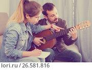 Купить «guitar tutor explaining basics to his female client at home», фото № 26581816, снято 4 марта 2017 г. (c) Яков Филимонов / Фотобанк Лори