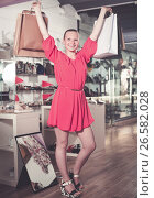Купить «Smiling female customer showing new purchases», фото № 26582028, снято 27 мая 2017 г. (c) Яков Филимонов / Фотобанк Лори