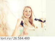 Купить «woman with styling iron doing her hair at bathroom», фото № 26584480, снято 13 февраля 2016 г. (c) Syda Productions / Фотобанк Лори