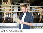 Купить «man with clipboard and milking cows on dairy farm», фото № 26585188, снято 12 августа 2016 г. (c) Syda Productions / Фотобанк Лори