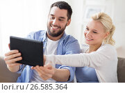 Купить «smiling happy couple with tablet pc at home», фото № 26585364, снято 11 февраля 2017 г. (c) Syda Productions / Фотобанк Лори