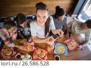 Купить «Young woman with friends photographing food in restaurant», фото № 26586528, снято 14 ноября 2016 г. (c) Wavebreak Media / Фотобанк Лори
