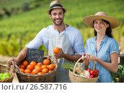 Smiling man and woman standing by fresh vegetables at farmer market. Стоковое фото, агентство Wavebreak Media / Фотобанк Лори