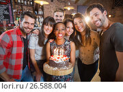Купить «Portrait of happy friends holding birthday cake», фото № 26588004, снято 14 ноября 2016 г. (c) Wavebreak Media / Фотобанк Лори