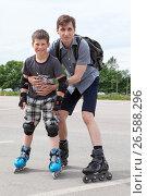 Купить «Папа с сыном катаются на роликовых коньках на асфальте», фото № 26588296, снято 18 июня 2017 г. (c) Кекяляйнен Андрей / Фотобанк Лори