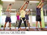 group of people with kettlebells exercising in gym. Стоковое фото, фотограф Syda Productions / Фотобанк Лори