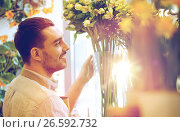 Купить «happy smiling florist man at flower shop», фото № 26592732, снято 27 марта 2016 г. (c) Syda Productions / Фотобанк Лори
