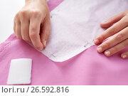 Купить «woman with pins stitching paper pattern to fabric», фото № 26592816, снято 29 сентября 2016 г. (c) Syda Productions / Фотобанк Лори