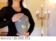 Купить «close up of woman with cremation urn in church», фото № 26593372, снято 20 марта 2017 г. (c) Syda Productions / Фотобанк Лори
