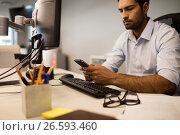 Купить «Businessman using mobile phone while sitting at office», фото № 26593460, снято 26 ноября 2016 г. (c) Wavebreak Media / Фотобанк Лори