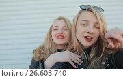Купить «Two young beautiful girlfriends blonde fun and coquettish posing in front of the camera. Do selfie. Spring», видеоролик № 26603740, снято 12 мая 2017 г. (c) Mikhail Davidovich / Фотобанк Лори