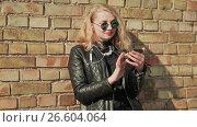 Купить «Stylish young blonde in sunglasses and leather jacket listening to music on bluetooth headphones in a mobile phone. Enjoy music. Spring. Background of a brick wall.», видеоролик № 26604064, снято 12 мая 2017 г. (c) Mikhail Davidovich / Фотобанк Лори