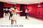Купить «Young smiling people having dancing class in studio», видеоролик № 26604304, снято 26 июня 2017 г. (c) Яков Филимонов / Фотобанк Лори