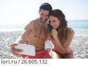 Купить «Happy couple taking selfie while sitting at beach», фото № 26605132, снято 17 января 2017 г. (c) Wavebreak Media / Фотобанк Лори