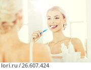 Купить «woman with toothbrush cleaning teeth at bathroom», фото № 26607424, снято 13 февраля 2016 г. (c) Syda Productions / Фотобанк Лори