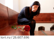 Купить «crying woman with red rose at funeral in church», фото № 26607696, снято 20 марта 2017 г. (c) Syda Productions / Фотобанк Лори