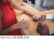 Купить «Couple holding their hands while having whisky at counter», фото № 26608216, снято 13 марта 2017 г. (c) Wavebreak Media / Фотобанк Лори