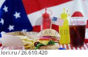 Купить «Hamburger and cold drink arranged on tablecloth», видеоролик № 26610420, снято 27 апреля 2018 г. (c) Wavebreak Media / Фотобанк Лори