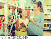 Купить «Female with girl choosing goods in food department», фото № 26632640, снято 5 июня 2017 г. (c) Яков Филимонов / Фотобанк Лори